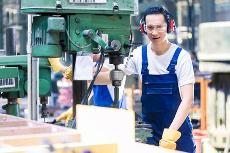 Trabajador de fábrica que opera la máquina para el procesamiento de metales en la planta de producción de Asia