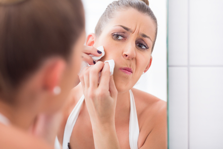 Woman popping pimples in front of bathroom mirror Stock Photo
