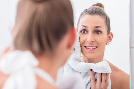 bathroom tiles: Young woman in bathroom towelling face while looking in mirror Stock Photo