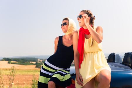 Two women sitting on hood of convertible car having summer trip