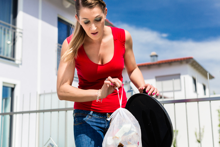 chores: Woman throwing the garbage away in container