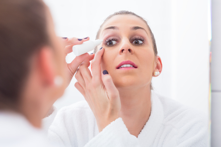 Young woman applying eye drops while looking in the bathroom mirror