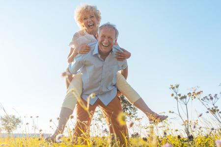 Flachwinkelansichtporträt eines glücklichen älteren lachenden Mannes beim Tragen seines Partners auf seinem zurück, an einem sonnigen Tag des Sommers in der Landschaft