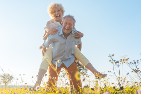 Ritratto di vista di angolo basso di un uomo senior felice che ride mentre portando il suo partner sulla sua schiena, in un giorno soleggiato dell'estate nella campagna