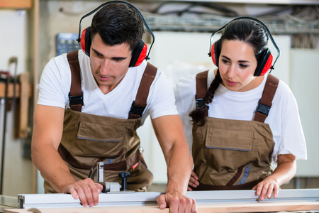 Carpenter and apprentice working together in wood workshop Stock Photo