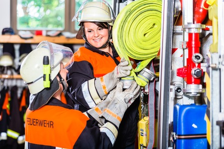 Female fire fighters loading hoses into fire engine Stock Photo