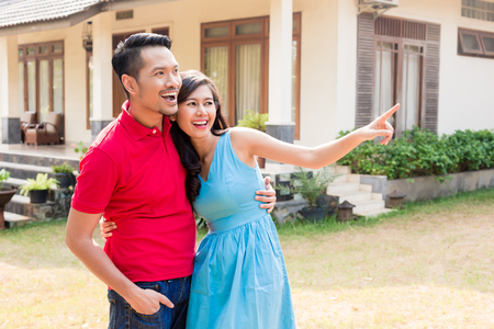 Cheerful young couple looking in the same direction in front of a cozy residential property
