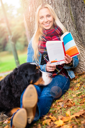 Woman with her Bernese mountain dog reading book in autumn park sitting on meadow covered with foliage