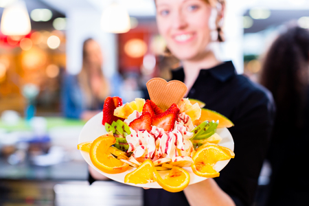 Saleswoman presenting fruit ice cream in cafe Stock Photo
