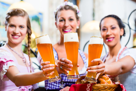 Group of people with wheat beer in Bavarian pub clinking glasses
