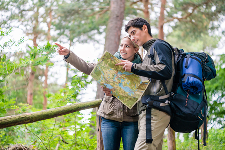 Young couple, woman and man, on hike looking for the right trail on map Stockfoto