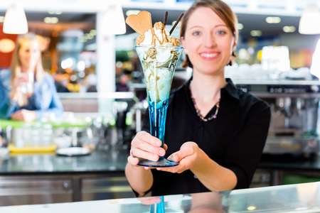 Saleswoman in ice cream parlor presenting sundae