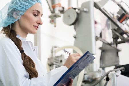 Dedicated female engineer writing a technical report while supervising the manufacturing process in a contemporary cosmetics factory 写真素材