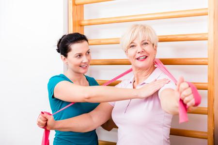 Senior patient doing therapeutic rehabilitation exercises at gymnasium ladder