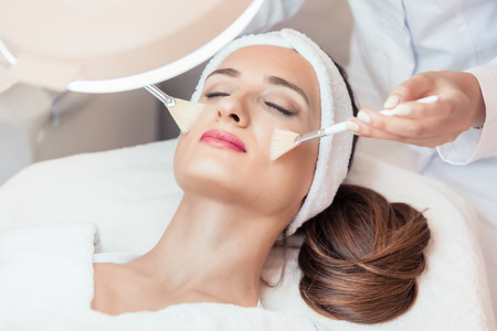 High-angle close-up view of the face of a beautiful woman during anti-aging facial massage with soft brushes in a modern cosmetic center Stock Photo