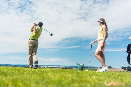 Full length of a young woman smiling while practicing the correct move for striking during golf class with a skilled professional player outdoors Stockfoto