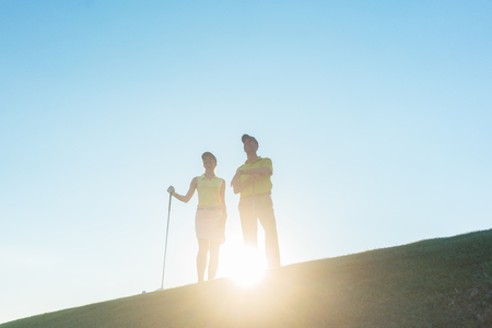 Low-angle view of the silhouette of a man pointing to the horizon while standing next to his female partner, on a professional golf course against sunshine and clear blue sky