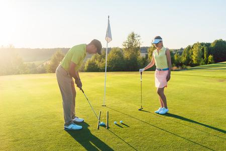 여름에 현대 컨트리 클럽에서 그의 게임 파트너와 짧은 샷을 운동하는 동안 구멍에 골프 공을 칠 준비가 남자의 전체 길이 측면보기 스톡 콘텐츠