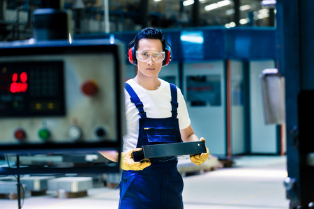 Asian machine operator in production plant checking data Stock Photo
