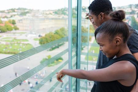 Young woman pointing while looking through the window with her boyfriend in a modern building