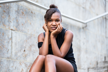 Portrait of young African American woman looking at camera while sitting on stairs in the city