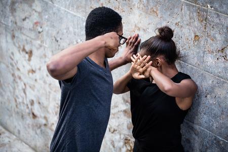 屋外に彼の拳で彼のガール フレンドを脅かす暴力的な若者