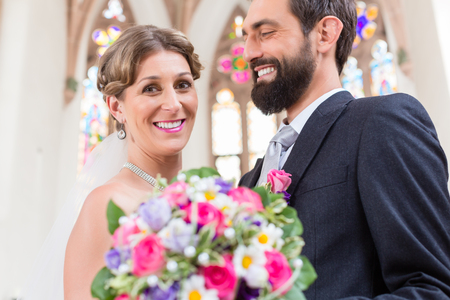 marrying: Bridal couple in church with flower bouquet