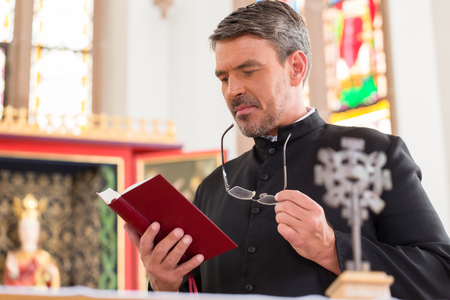 Priest reading bible in church standing at altar Foto de archivo