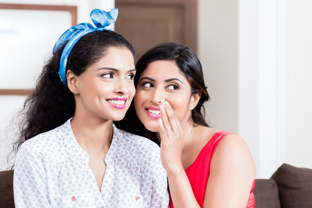 Young woman whispering to her best friend gossips or funny secrets indoors Stock Photo