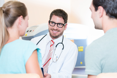 Pregnant woman and her partner seeing physician for pregnancy examination