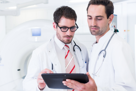 Doctors discussing images of x-ray scan standing in front of CT machine in hospital Stock Photo