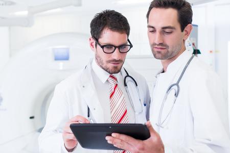 Médicos discutiendo imágenes de escáner de rayos X de pie frente a la máquina de TC en el hospital Foto de archivo