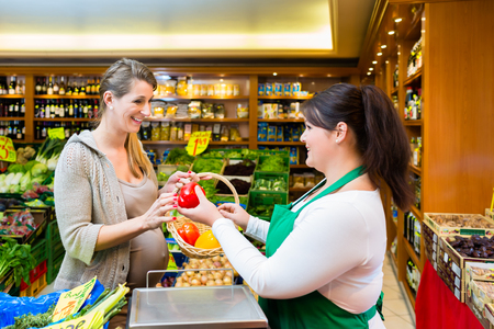 Sales lady handing vegetables to woman in grocer store Stockfoto