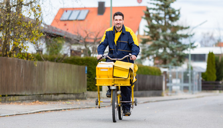 Postman riding his cargo bike carrying out mail in neighborhood Stock Photo