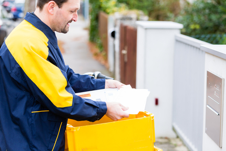 Postman delivering letters to mailbox of recipient Stock Photo