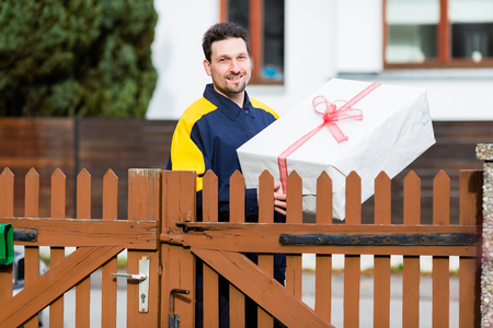 Postman delivering packet wrapped as present Stock Photo