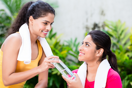 Cheerful young woman giving a bottle of natural plain water to her friend during workout session Stock Photo