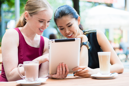 Two young female best friends smiling while using a tablet PC outdoors at a trendy location downtown Stock Photo