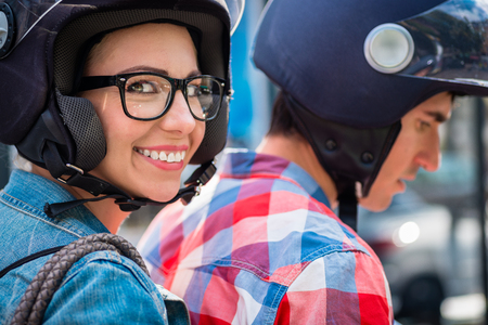 Smiling girl with glasses sitting on pillion seat of scooter