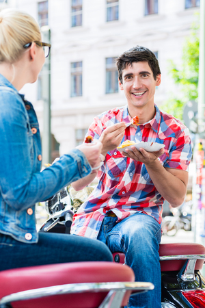 Tourist couple taking rest during scooter tour through berlin and eating currywurst and chips Stock Photo