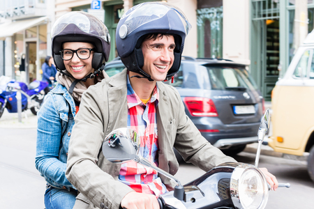 Young woman with helmet sitting on pillion seat of Vespa in streets of Berlin Archivio Fotografico