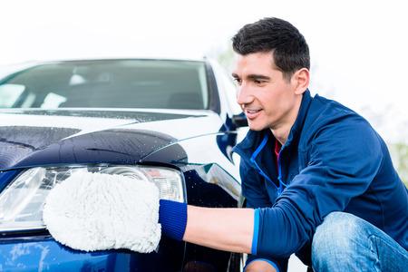 Hart arbeitender junger Mann, der Auto mit weißem microfiber Handschuh bei der Selbstwäsche poliert Standard-Bild - 88454275