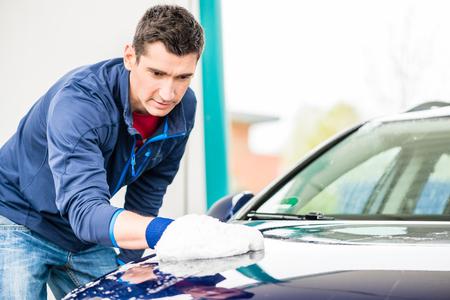 mitt: Hard-working young man polishing car with white microfiber mitt at auto wash