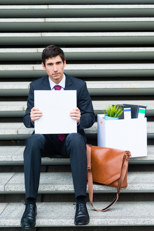 Worried unemployed businessman sitting on a flight of concrete steps in town with his office contents and blank sign seeking employment