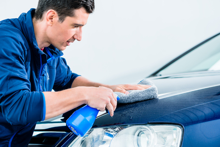 Proud car owner cleaning his vehicle with a sponge and detergent in a spray bottle , close up cropped profile view Stock Photo