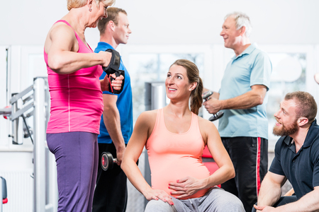 Pregnant woman with senior people working out at the gym with personal trainer Stock Photo