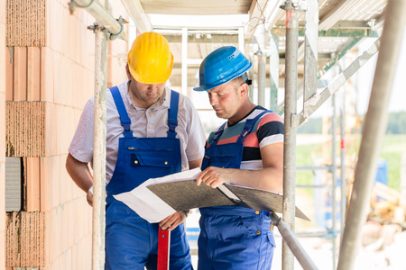 2 scaffold stock photos royalty free 2 scaffold images two construction workers on site with helmets having discussion in scaffold with plans or blueprints malvernweather Image collections