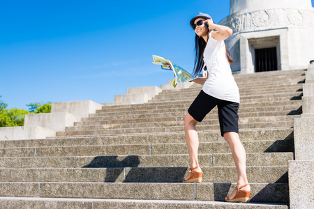 Happy young Asian tourist climbing stairs towards an ancient landmark Stock Photo