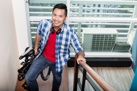 Young asian professional  coming home after work and carrying collapsible bicycle up the stairs to his apartment Stock Photo