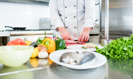 Chef preparing vegetables and fish for cooking in his kitchen